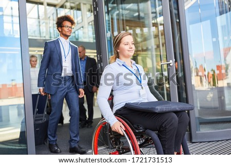 Smiling businesswoman in a wheelchair leaves the barrier-free business company Stock foto ©