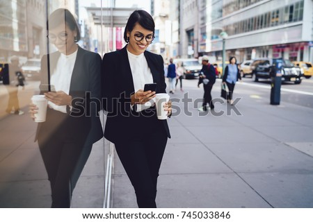 Smiling businesswoman in formal wear satisfied with getting good news on email while walking on street during coffee break, successful female trader sending messages on mobile holding takeaway cup