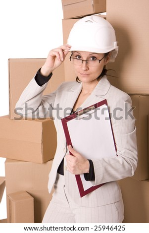 smiling businesswoman in helmet correcting glasses and keeping clipboard, on cardboard boxes background