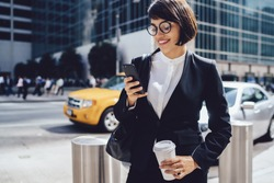 Smiling businesswoman in stylish eyewear dialling number on mobile for calling taxi while standing on city street, prosperous female manager waiting for cab sending message and holding coffee to go