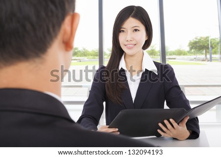 smiling businesswoman interviewing with businessman in office