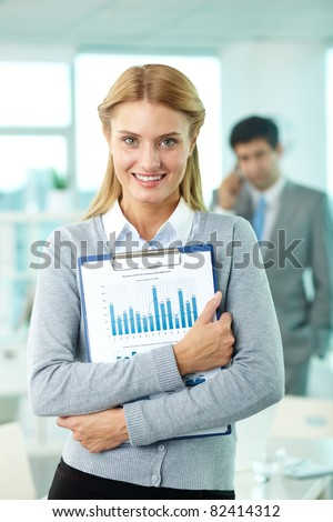 Smiling businesswoman looking at camera in working environment