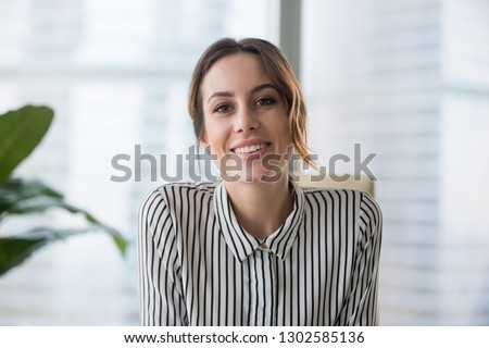 Smiling businesswoman looking at camera webcam make conference business call, recording video blog, talking with client, distance job interview, e-coaching, online training concept, headshot portrait