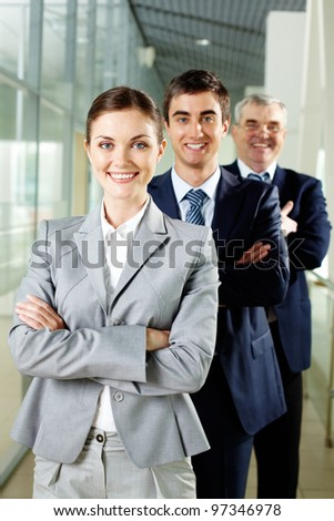 Smiling businesswoman looking at camera with two men behind