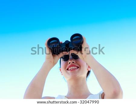 Smiling businesswoman looking through binoculars against blue sky