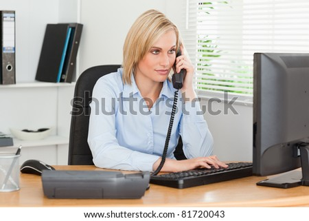 Smiling businesswoman on the phone looking at her screen in her office