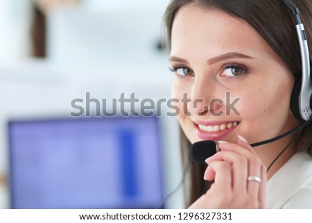 Smiling businesswoman or helpline operator with headset and computer at office #1296327331