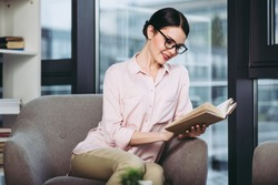 smiling businesswoman reading the book and sitting in armchair