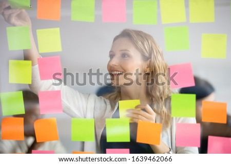 Smiling businesswoman removing sticky papers with finished tasks from scrum board, colorful post it notes, successful happy leader coach planning corporate project at glass wall, adding ideas Stockfoto ©
