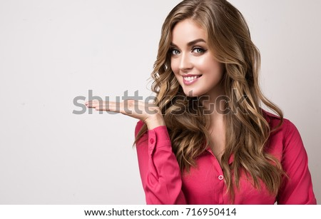 Smiling businesswoman showing your product .Beautiful girl  with curly hair  pointing to the side . Presenting your product. Expressive facial expressions #716950414
