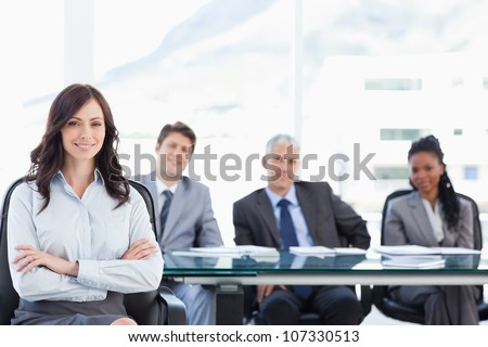 Smiling businesswoman sitting and crossing her arms while accompanied by her team