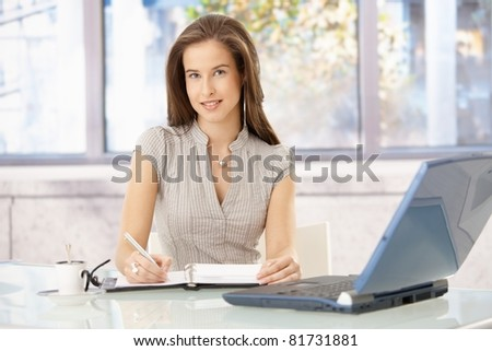 Smiling businesswoman sitting at desk in office, writing into personal organizer, looking at camera.?