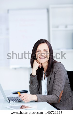 Smiling businesswoman sitting in front of her laptop inside the office