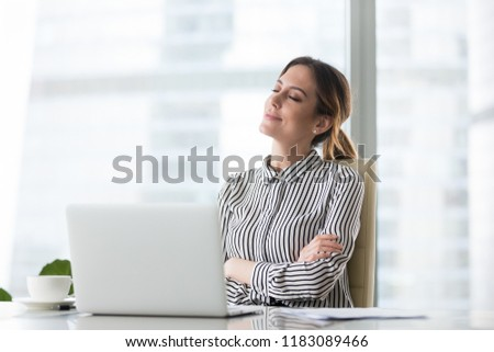 Smiling businesswoman sitting in office chair relaxing with eyes closed, calm female worker or woman ceo feeling peaceful resting at workplace dreaming about positive things distracted from work