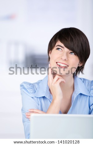 Smiling businesswoman sitting thinking behind her laptop computer looking up into the air