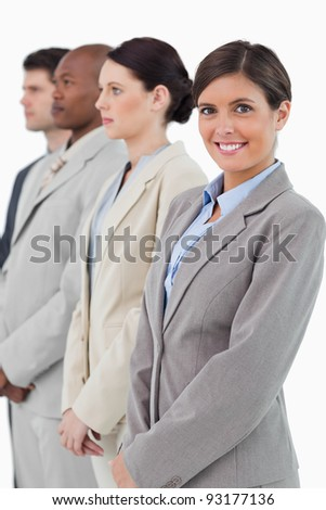 Smiling businesswoman standing next to her associates against a white background