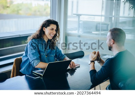 Smiling businesswoman taking interview of a job applicant. Friendly recruitment manager interviewing young man in office boardroom.