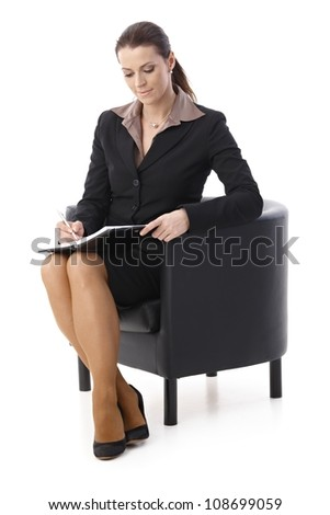 Smiling businesswoman taking notes into personal calendar, sitting in armchair, isolated on white.