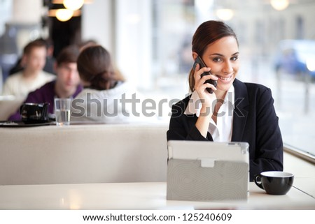 Smiling businesswoman talking on the phone and using tablet computer in a coffee shop