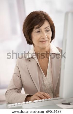 Smiling businesswoman using desktop computer in office.?