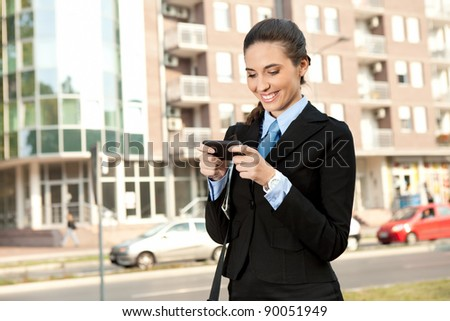 smiling businesswoman using  smart phone, outdoor