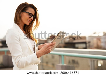 Smiling businesswoman using tablet and working. Beautiful businesswoman outdoors Foto stock ©