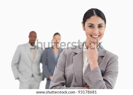 Smiling businesswoman with associates behind her against a white background