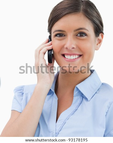 Smiling businesswoman with cellphone against a white background