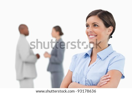 Smiling businesswoman with crossed arms and colleagues behind her against a white background