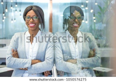 Smiling businesswoman with crossed arms posing in office with reflection in the glass.