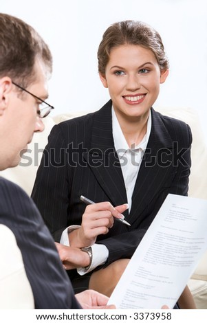 Smiling businesswoman with pan in her hand sitting on the sofa and businessman sitting near by reading the document