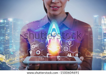 Smiling businesswoman with tablet standing in night city with double exposure of startup interface. Concept of new project launch. Toned image