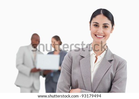 Smiling businesswoman with talking colleagues behind her against a white background