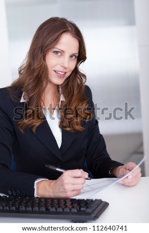 Smiling businesswoman working at her computer in the office