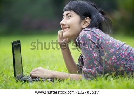 Smiling businesswoman working with laptop outdoor