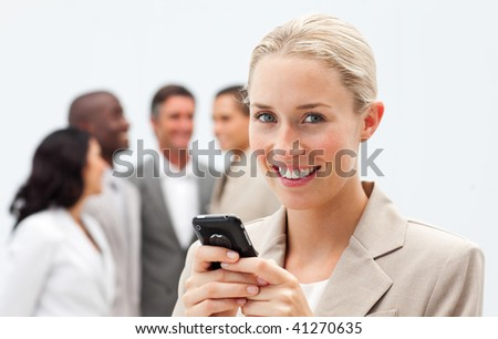 Smiling businesswoman writing a message with a mobile phone in workplace with her