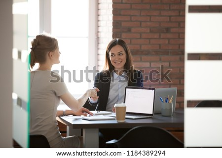 Smiling businesswomen colleagues handshaking in office thanking for successful teamwork help support, making deal at meeting, manager shakes hand of satisfied client, hr hiring employee at interview
