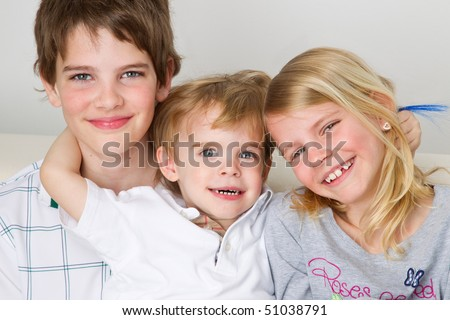 Smiling cadet sits between his brother and his sister