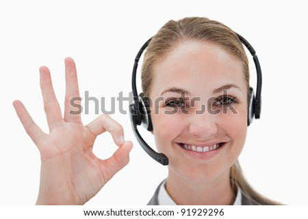 Smiling call center agent approving against a white background