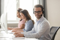 Smiling call center male worker pose looking at camera girls colleagues on background, sales agent wearing headset use pc answers incoming phone calls, provide professional support to customer concept