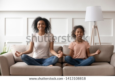 Photo of Smiling calm african family healthy mom teaching yoga cute little kid daughter doing exercises sit on sofa in lotus pose, happy mindful mixed race mother and child girl meditating together at home