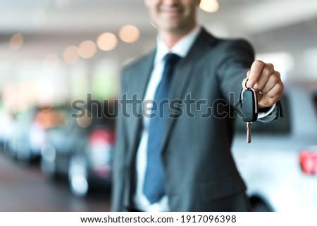 Smiling car salesman handing over your new car keys, dealership and sales concept