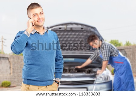 Smiling careless guy talking on a cell phone while in the background mechanic is checking his car