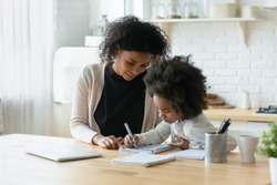 Smiling caring African American mother helping to adorable little daughter with homework, sitting at table in modern kitchen, pretty girl doing school tasks, studying, writing with pen, homeschooling