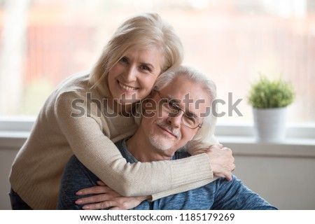 Smiling caring middle aged wife embracing senior husband at home, happy old woman hugging loving mature man looking at camera, retired elderly family married couple dating bonding headshot portrait