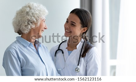 Smiling caring young female nurse doctor caretaker assisting happy senior grandma helping old patient in rehabilitation recovery at medical checkup visit, elder people healthcare homecare concept