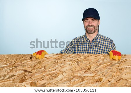 Smiling carpenter holds a sheet of plywood.