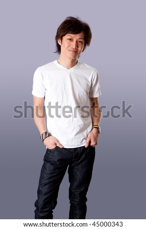 Smiling casual Asian man wearing white shirt and jeans standing with hands in pockets and happy expression, isolated.