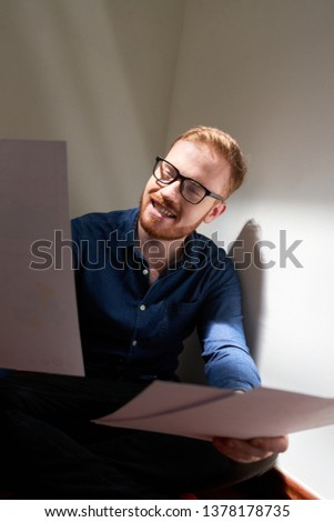 Smiling casual businessman in casual clothing sitting and examining documents and contracts