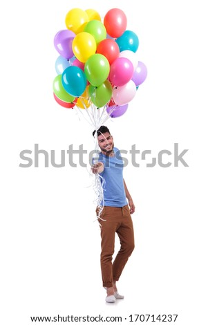 smiling casual man is offering a bunch of baloons on white background